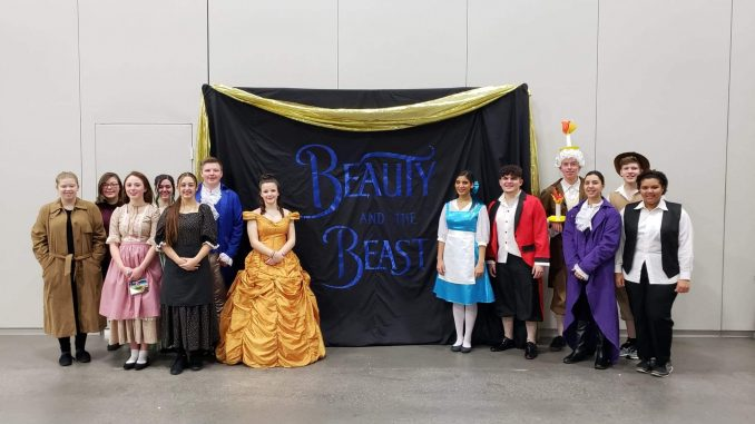 Lynn Camp students are shown in costume in front of a Beauty and the Beast backdrop.