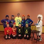Students dressed up in characters are shown in the hotel lobby.
