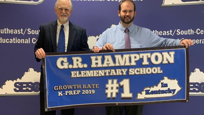 David Johnson is shown presenting Brian Frederick with a banner for being the top elementary school for growth on last year's assessment.