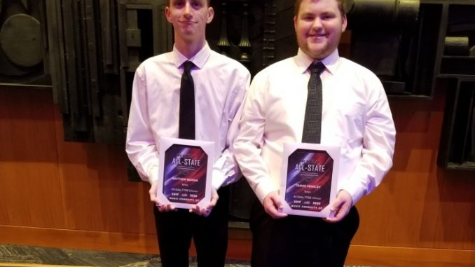 Two male choir students hold their award plaques