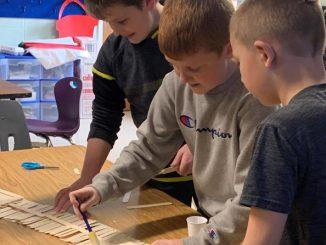 Three boys are shown gluing craft sticks.