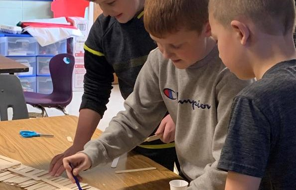 Three boys are shown gluing craft sticks.