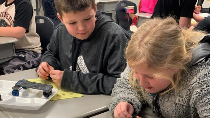 Two students are shown inspecting parts in their robotics kit in the classroom.