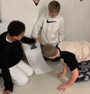 Three students are shown launching their robot from the top of the card board paper ramp taped to the wall.