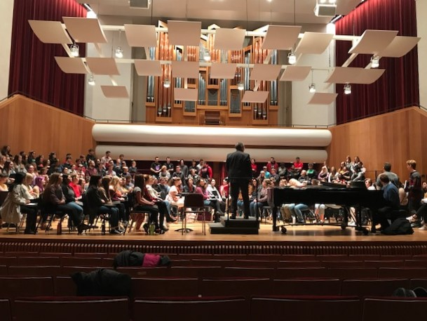 Students shown with UofL singers rehearsing