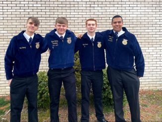 Four Lynn Camp FFA offers pose for a photo in their signature blue jackets.
