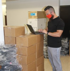 Doug Cobb is shown preparing a Chromebook for student use.