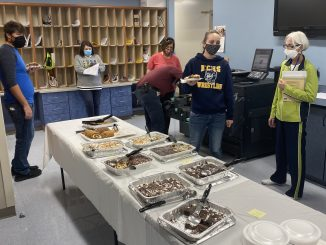 Staff members are shown in the work room at Knox Central with a dessert table in the center.