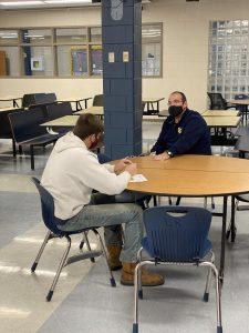 Students and teachers shown discussing progress in the lunchroom.