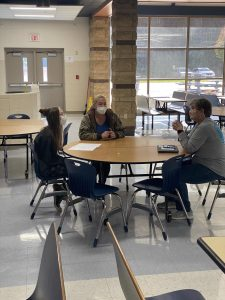 Student, parent and teacher shown discussing progress in the lunchroom.