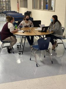 Students, family members, and teachers shown discussing progress in the lunchroom.