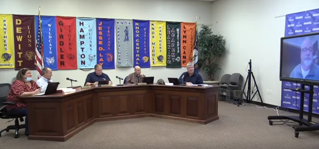 Members shown seated during December meeting with Superintendent video conferencing