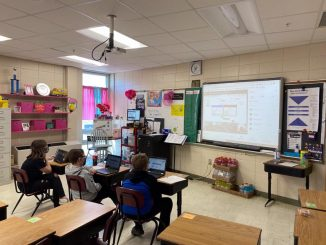 Classroom shown with students viewing teams on SmartBoard.