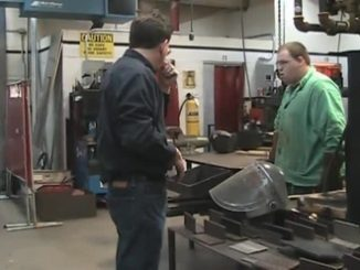 Welding instructor Monty Bingham is shown demonstrating a skill to a student.