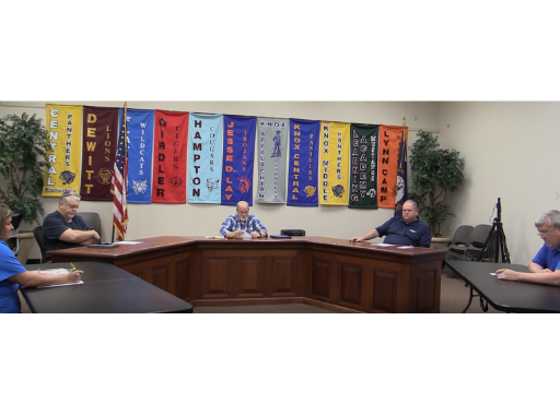 Board members are shown at the table calling the May 4 meeting to order.