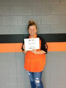 Julia shown receiving $1,000 scholarship