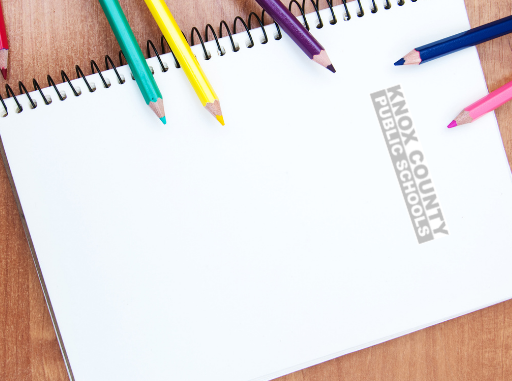 Notebook with KCPS logo and color pencils scattered.