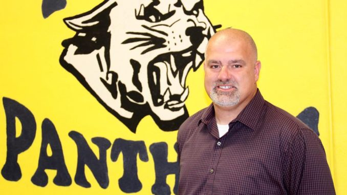 Photo of Fred Hoskins in front of a KCMS Panther backdrop