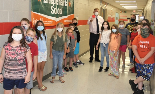 Students shown in hallway with Principal Mays earning a Tiger Paw for their class.