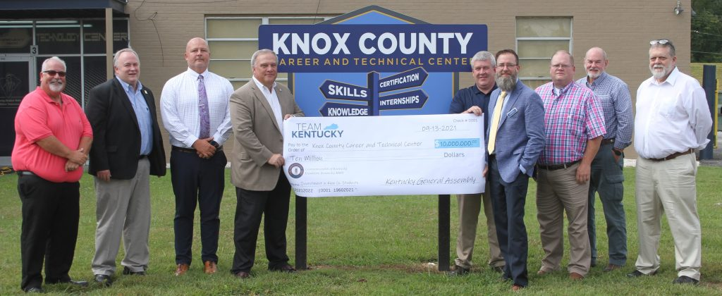 School and local leaders hold a check in front of the Knox County CTC sign.